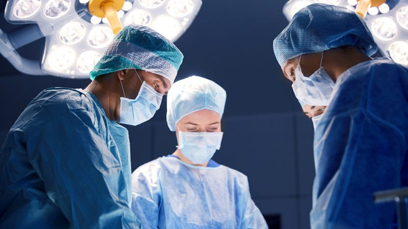 surgery, medicine and people concept - group of surgeons at operation in operating room at hospital