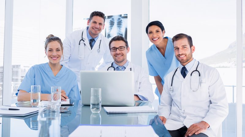 Portrait of a happy medical team using laptop together in the office