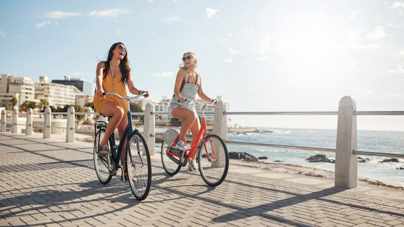 female-friends-riding-their-bicycles-on-the-promen-PG7NNP9.jpg