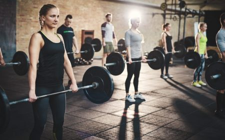 Group of strong male and female adults holding heavy barbells in ftness exercise studio with thick mats on floor and brick walls